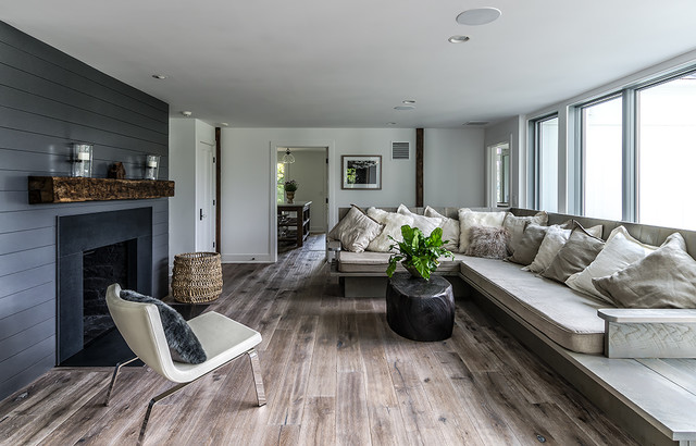 Distressed Hardwood Flooring Living Room Farmhouse with Black Paneling Chair Cushions Fireplace Mantle Neutral Colors Sofa