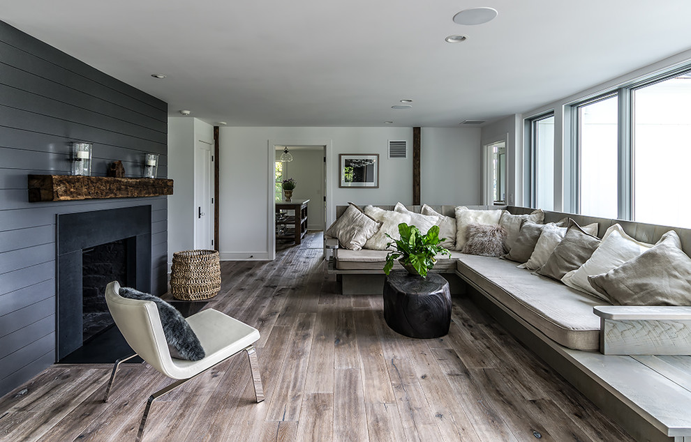 Distressed Hardwood Flooring Living Room Farmhouse with Black Paneling Chair Cushions Fireplace Mantle Neutral
