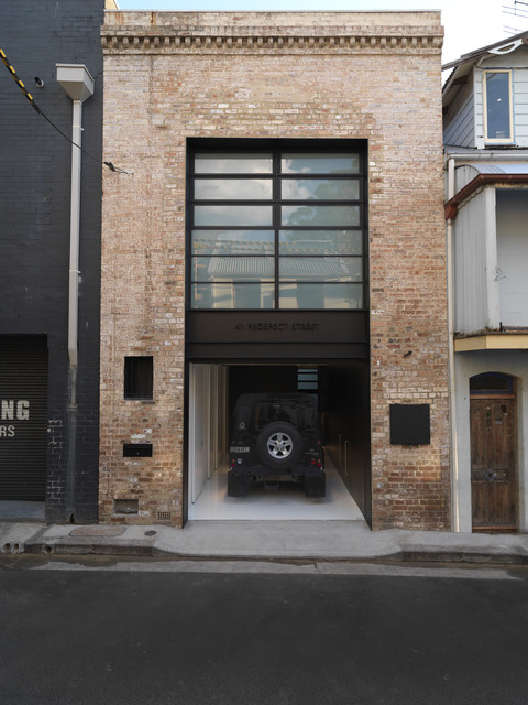 mackenzie childs outlet Garage And Shed Industrial with black brick wall entrance entry epoxy floor garage door