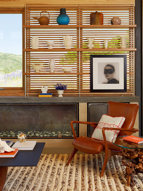 Vladimir Kagan Family Room Contemporary with Area Rug Concrete Fireplace Open Shelving Seating Area Stones