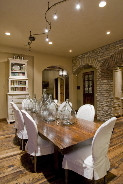 wingback chair slipcover Dining Room Mediterranean with archway bottles glass front bookshelf hardwood floors slipcovered dining