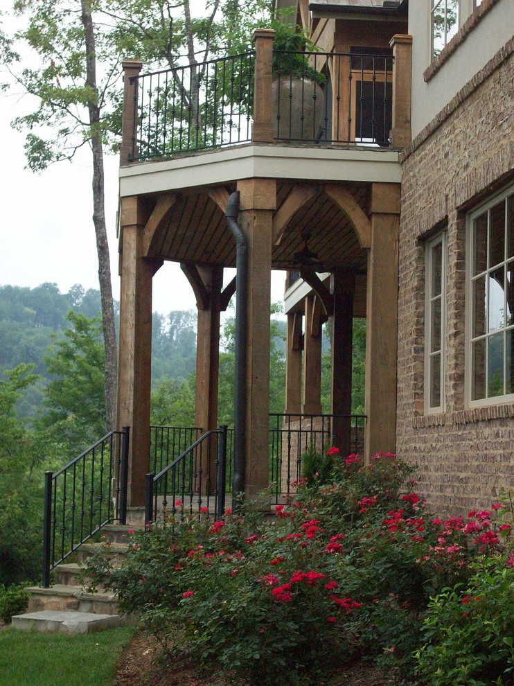 Wrought iron railing exterior traditional with arches balcony brick foundation planting porch for Wrought iron balcony railings exterior