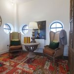 8 Round Rugs with Eclectic Home Office and  Patchwork Area Rug  White Walls     Red  Rattan Wingback Chairs  Velvet Pillows