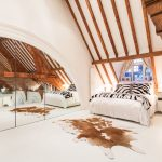 Animal Skin Rugs with Contemporary Bedroom and  Exposed Beams  Large Bedroom Mirror  White Floorboards  Arched Window  Painted Floorboards