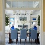 Blue Area Rugs with Beach Style Dining Room and  Transom Window  White and Blue Framed Art  Chandelier  Dutch Colonial Style  Dark Wood Dining Table