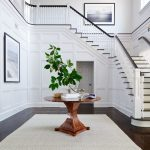 Chevron Area Rug with Traditional Entry and  Entry Table  Chevron Area Rug  Staircase  Round Wood Table  White Wall Paneling