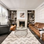 Chevron Area Rug with Transitional Living Room and  Built in Shelves  Brown Leather Sofa  Brown Leather Ottoman  Gray Carpet  Modern Fireplace