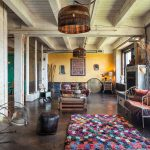 Colorful Area Rugs with Industrial Living Room and  Painted Wood Ceiling  Wooden Crates Coffee Table  Concrete Walls  Dark Leather Cube Stool  Colorful Checkerboard Rug