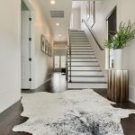 Cow Hide Rug with Contemporary Staircase and  Wall Art  Dark Wood Floor  Iron Stair Railing  Hallway  White Vase
