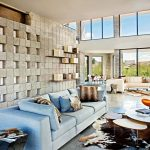Cow Hide Rug with Modern Family Room and  Large Windows  Stone and Glass Wall  Orange Chair  Emu  Wood Shelves