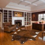 Cow Hide Rug with Traditional Home Office and  Brown Leather Ottoman  Brown Leather Armchair  Animal Hide Rug  Built in Bookcase  Brown Wall