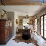 Cow Hide Rug with Traditional Home Office and  Gilt Frames  Lantern  Woven Rug     Wood Lintel  Tufted Ottoman