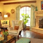 Cow Hide Rug with Traditional Living Room and  Large Area Rug  Artwork Above Fireplace  Tufted Arm Chair     Dark Wood Window Trim  Exposed Beams