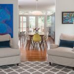 Gray and White Rug with Contemporary Dining Room and  Abstract Art  Blue Back Pillows  White Dining Chairs  Silver Floor Lamp  White Pendant Light