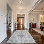 Gray and White Rug with Farmhouse Entry and  Rustic Hardwood Flooring  Tall Ceiling  Grey and White Rug  Hanging Gold Pendants  Beige Walls