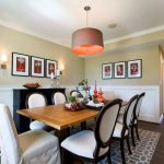 Gray and White Rug with Transitional Dining Room and  Hardwood Flooring  Dining Room Sconces  White Ceiling  White Wainscoting  Pop of Color