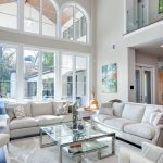 Gray Area Rugs with Contemporary Living Room and  Arched Windows  Glass Top Coffee Table  Cream Color Sofa  Beige Sofa  Globe Chandelier