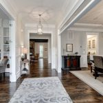 Grey and White Rug with Farmhouse Entry and  White Wainscoting     Hanging Gold Pendants  Rustic Hardwood  Tall Ceiling  Gray and White Rug