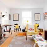 Home Goods Area Rugs with Eclectic Family Room and  Mismatched Furniture  White Bench  Yellow Striped Armchair  White Fireplace Mantel  Fireplace Screen