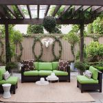 Hula Hoop Rug with Transitional Patio and  Wood Ceiling Beams  White Side Table  Stone Patio  Bushes  Fence Vines