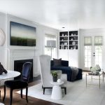 Navy and White Rug with Traditional Living Room and  		Black Bookshelf Backing  Roman Shades  White Chandelier  Bookshelves  Circular Dining Table