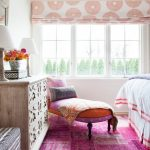 Pink Area Rug with Eclectic Bedroom and  Roman Shades  Pink Area Rug  Table Lamps  Natural Light  Distressed Drawers