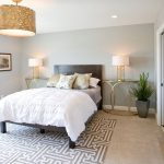 Rug on Carpet with Contemporary Bedroom and  Gold Nightstand  Gold Table Lamp  Yellow Throw Pillow     Gold Side Table  Wood Sunburst Mirror