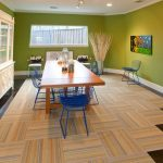 Rug on Carpet with Modern Dining Room and  Track Lights  Abstract Art  Wood Fence     Dining Table  Polished Stained Concrete