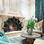 Turquoise Area Rug with Mediterranean Living Room and  High Ceilings  Round Coffee Table  Ornate  Carved Fireplace Mantel  Purple and Green Curtains