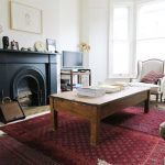 What is Rugged Individualism with Eclectic Living Room and  White Walls     Farrow and Ball Wimborne White  Rustic Coffee Table  Kilims  Black Fireplace