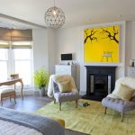 Yellow Area Rug with Beach Style Bedroom and  Small Wall Mounted Tv  Wooden Bedroom Floor  White Fur Throw  Black Mantle  Wooden Floor