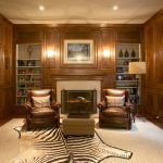 Zebra Skin Rug with Traditional Home Office and  Leather Arm Chairs  Built in Shelves  Dark Wood Paneling  Dark Stained Wood  Zebra Skin Rug